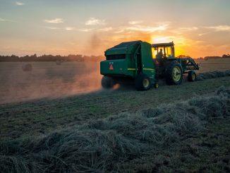 Un tracteur dans un champ, au coucher de soleil