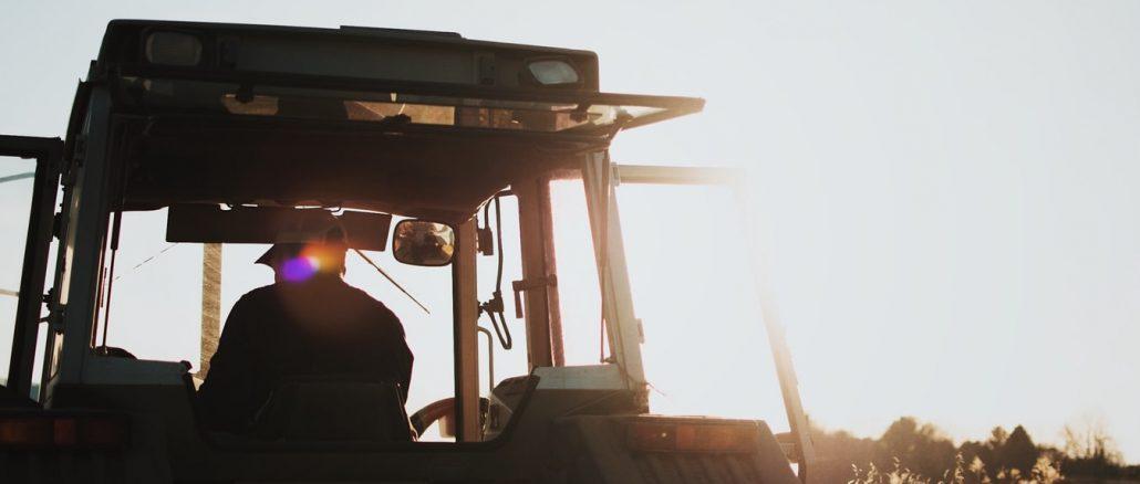 Un paysan sur son tracteur, au coucher de soleil