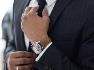 Un homme en costume, ajustant sa cravate