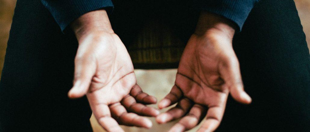 Une personne tendant les deux mains pour prier