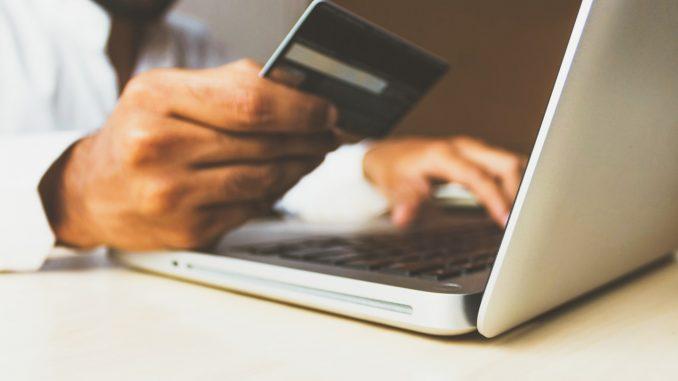 Un homme avec une carte bancaire devant son ordinateur.