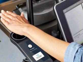 Une personne posant la main sur le dispositif Amazon One, la solution de paiement par empreinte palmaire.
