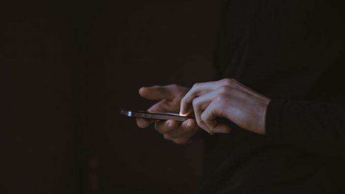 Une personne manipulant un smartphone dans le noir ( Photo : Unsplash).